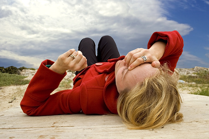 Woman with hand on her forehead on the ground after fainting